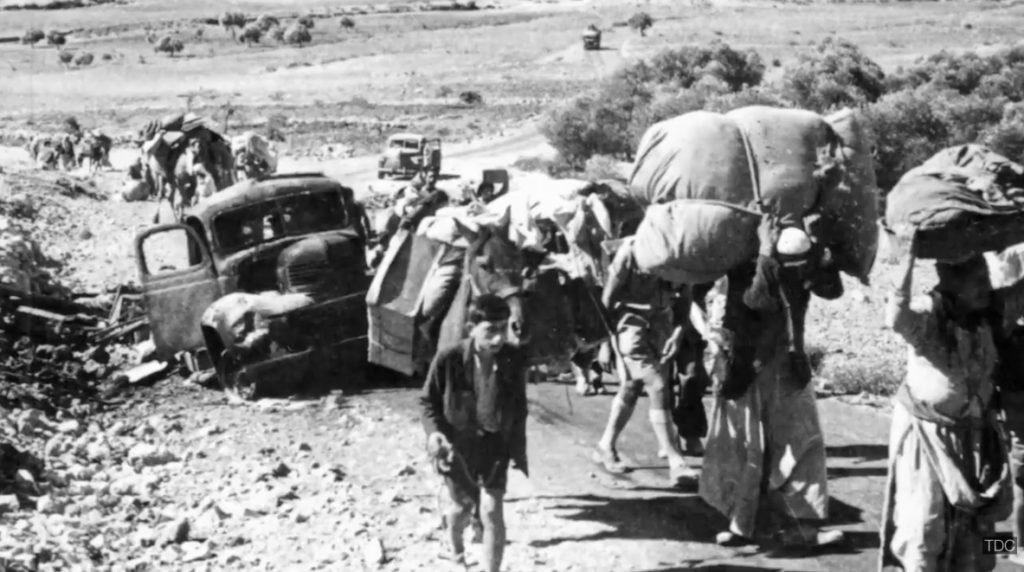Palestinian refugees laden with huge bundles of worldly possessions climb up a section of road to escape the Israeli massacres in their villages.