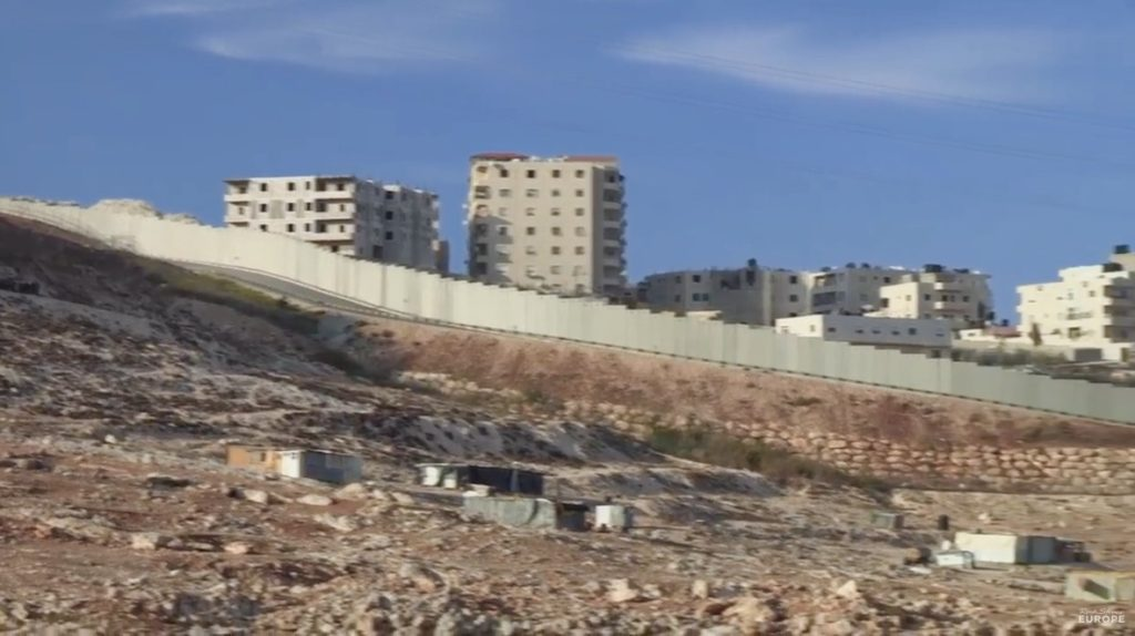 A few Palestinian buildings on desolate land in the foreground are dwarfed by a high wall surrounding numerous high rise buildings of an Israeli settlement in the background.